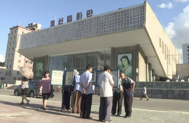 In this image made from video, people read newspapers displayed on the street in Pyongyang, North Korea, Friday, Aug. 11, 2017. Despite tensions and talk of war, life on the streets of the North Korean capital Pyongyang remained calm.