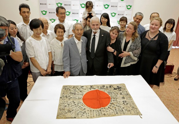 WWII veteran Marvin Strombo, center right, and Tatsuya Yasue, center left, pose with their relatives for photographers in front of a Japanese flag with autographed messages which was owned by his brother Sadao Yasue, who was killed in the Pacific during World Work II, during a press conference after a ceremony in Higashishirakawa, in central Japan's Gifu prefecture Tuesday, Aug. 15, 2017.