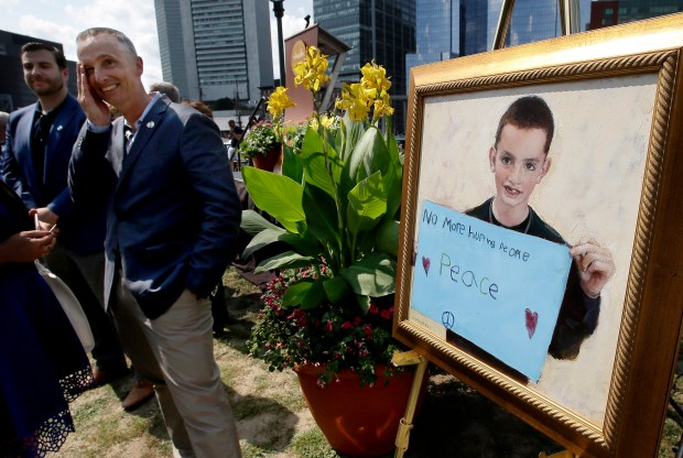 Bill Richard, second from left, father of fatal Boston Marathon bombing victim Martin Richard, brings his hand to his face while standing next to a painting of Martin, right, at the conclusion of groundbreaking ceremonies for a park named after his late son, Wednesday, Aug. 16, 2017, in Boston. Martin Richard, 8, was the youngest of three people killed when two bombs exploded near the Boston Marathon finish line on April 15, 2013.
