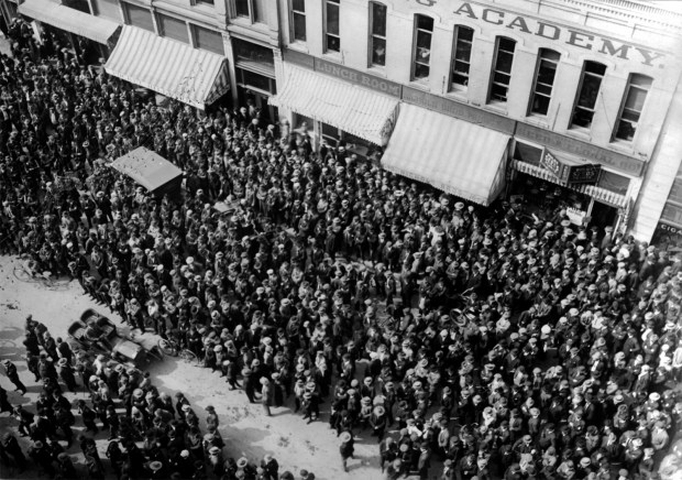 """It was typical in the early 1900's for crowds to gather in front of The Denver Post building to listen to sporting events and other big news. People crowd Champa Street by The Denver Post headquarters in downtown Denver between 1915 and 1925, probably to listen to a sporting event. Signs read: """"Lunch Room"""" and """"Seed and Floral Co."""""""