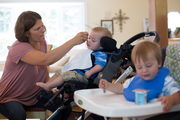 Erica Mumm feeds her son Christian, who has severe epilepsy, as his fraternal twin, Connor, feeds himself at their home in New Hartford, Connecticut. GlaxoSmithKline has promised to help the Mumms get the drug Christian needs despite its withdrawal from the market.