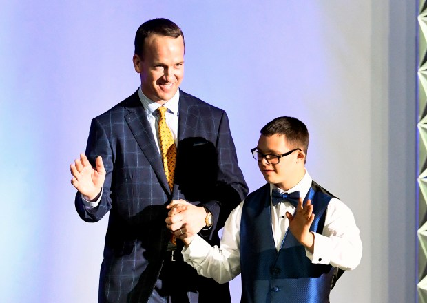 """Peyton Manning walks down the runway with model Louie Rotella, during the Global Down Syndrome Foundation's """"Be Beautiful, Be Yourself' fashion show at the Hyatt Regency Hotel in Denver on Nov. 12, 2016."""