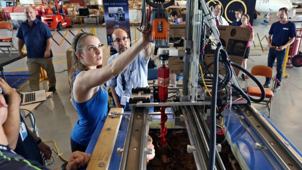 Colorado School of Mines student Caroline Ellis works on her team's water extraction system as Angel Abbud-Madrid, research associate professor in mechanical engineering and director of the Center for Space Resources at Mines, looks on at the Mars Ice Challenge at NASA's Langley Research Center in June 2017. Photo by Colorado School of Mines