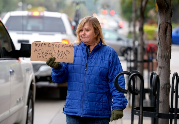 A woman panhandles in Boulder on Oct. 6, 2015. According to a recent Washington Post article, Americans' increasing reliance on non-cash forms of payment translates into a whole lot less generosity on the street.