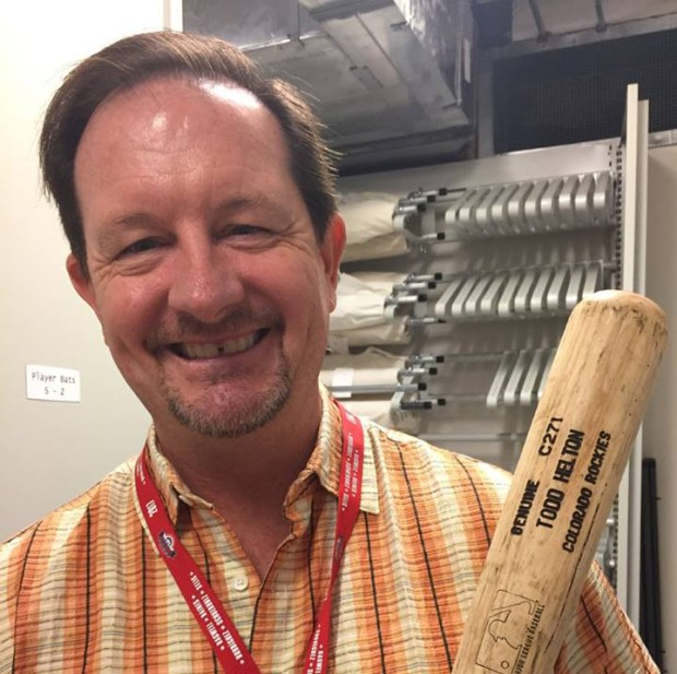 Colorado Rockies beat reporter Patrick Saunders holds Todd Helton's bat at the Baseball Hall of Fame in Cooperstown, N.Y.