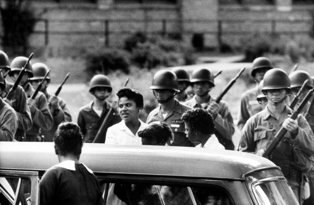 Minnijean Brown, 15, arrives with the  other members  of the Little Rock Nine outside Central High School in Little Rock, Ark., on Sept. 25, 1957, as members of the 101st Division  of the Airborne Command stand ready to protect them.