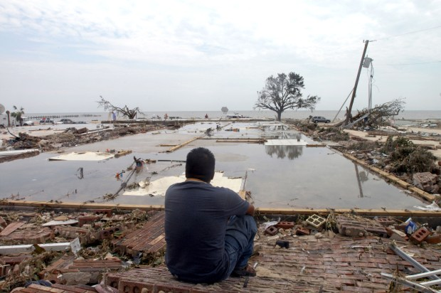 A man looks over the concrete slab that used to be his apartment on Aug. 30, 2005, in Biloxi, Miss.. after Hurricane Katrina tore through the Gulf Coast.