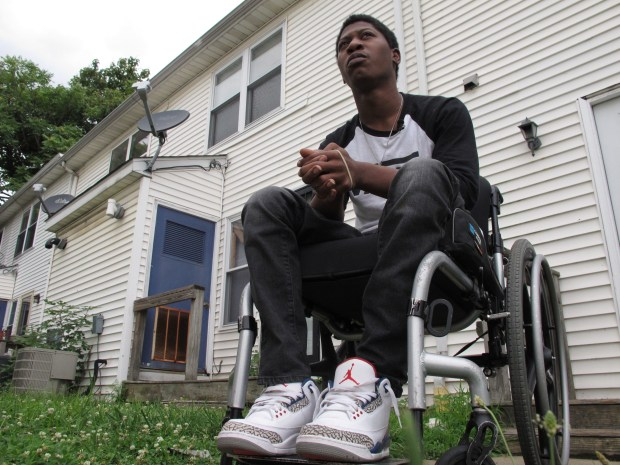 Rayquan Briscoe sits outside his home ...