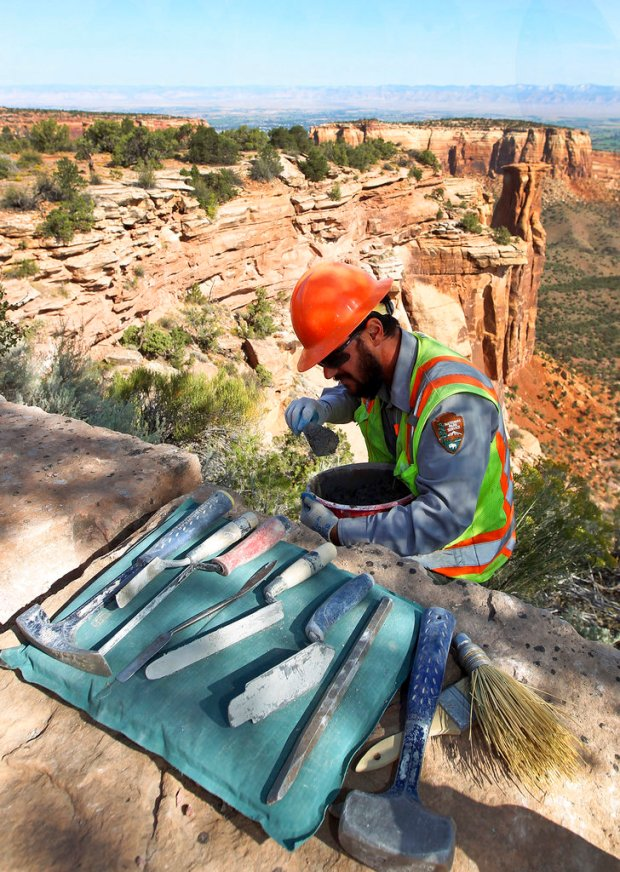 In this Sept. 11, 2017, photo, perched on a ledge above Monument Canyon, stonemason Scott Banjac, of Fruita, Colo., applies a special mortar in between the red sandstone rocks along Rimrock Drive as a crew of stone masons rebuild the rock guardrails in the Colorado National Monument near Fruita. The crew is using a mortar made of a lime, sand and Portland cement that is similar to the mortar that the original Civilian Conservation Corps builders of the wall used.