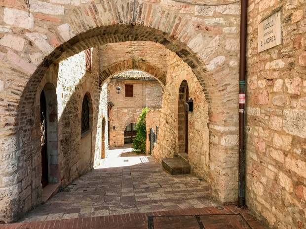 Assisi, Italy, in the Umbria region. The small town is filled with buildings made from a characteristic mixture of pink and tan limestone.