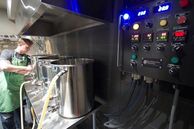 Kal Wallner looks over his kettles in his home brewery room in Ottawa, Canada.