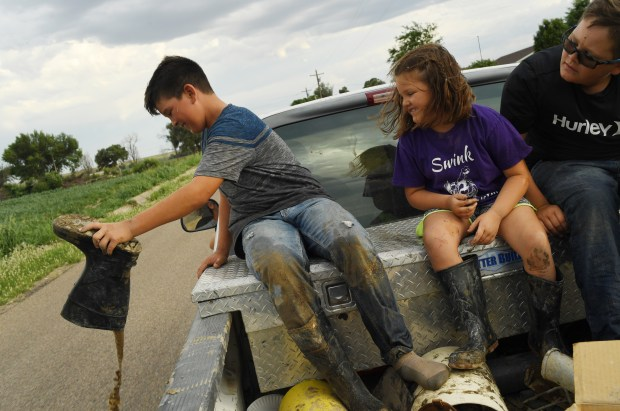 Chris Tomky, 37, took his whole family to help with irrigation at their family farm on July 11, 2017 in Rocky Ford. From left, Tanner, 11, dumbs water out of his boot as his sister Trista, 6, and brother Lincoln, 10, ride in the back of the pickup. Their father, Chris, mother, Jody, and other brother Jackson, 11, ride up front.