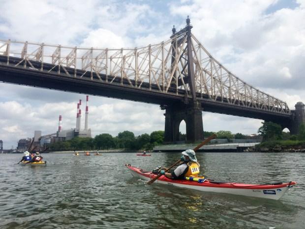 Paddlers pass under the Queensboro Bridge.