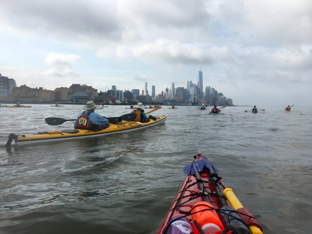 Paddlers head down the Hudson River, with Lower Manhattan in the distance.