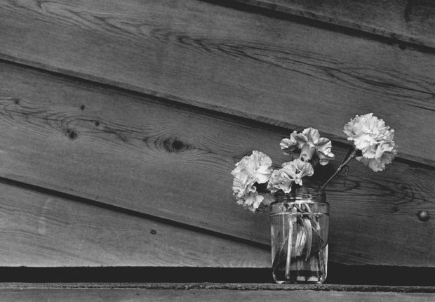 Flowers in a glass jar vase sit outside the garage door in 1985 where Alan Berg was killed almost one year earlier.
