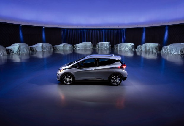 This photo provided by General Motors Co. shows a Chevrolet Bolt, surrounded by nine electric and fuel cell vehicles covered by tarps. On Oct. 2, GM announced the company will produce two new electric vehicles on the Bolt underpinnings in the next 18 months and 20 electric and hydrogen fuel cell vehicles by 2023.
