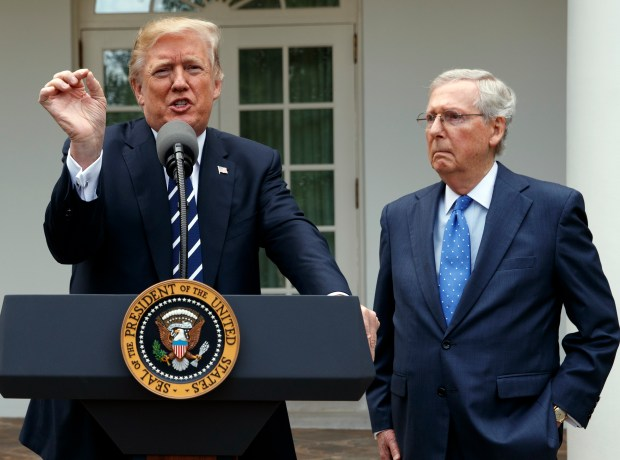 Senate Majority Leader Mitch McConnell listens as President Donald Trump speaks with reporters in the Rose Garden of the White House on Oct. 16.