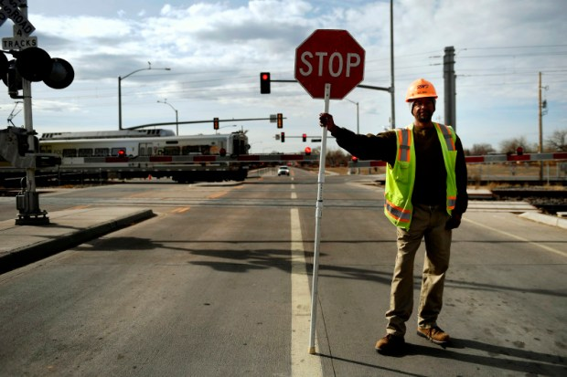 """A crossing guard stops traffic at the Smith Road and Sable Boulevard A-Line crossing in Aurora. Because of technological glitches with crossing arms, RTD's trains much sound their horns at all crossings, despite the agency's promises of """"quiet zones"""" along the A-Line."""