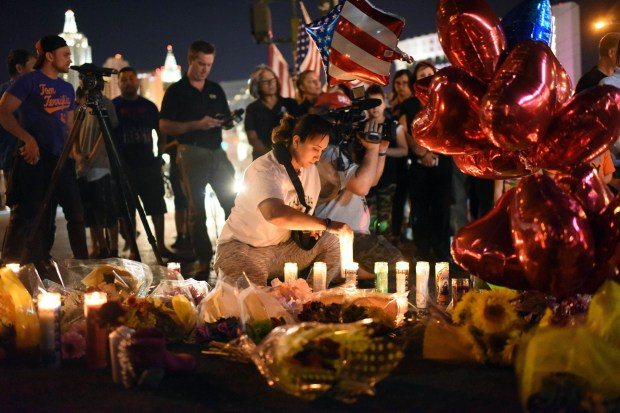A woman lights a candle at a makeshift memorial near the Mandalay Hotel on the Las Vegas Strip on Tuesday -- two days after a gunman killed 59 people and wounded more than 500 others.