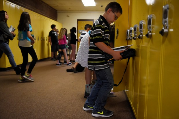 Ryan Kilburn checks his schedule before leaving a bank of lockers at Overland Trail Middle School on Aug. 17, 2017, in Brighton.