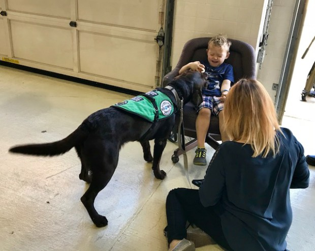 Kate Rondelli and her son Mylon, 4, visit the Bunker Hill Fire Station in Brentwood, Maryland with Slash, a chocolate Lab who has been trained to detect diabetic emergencies.