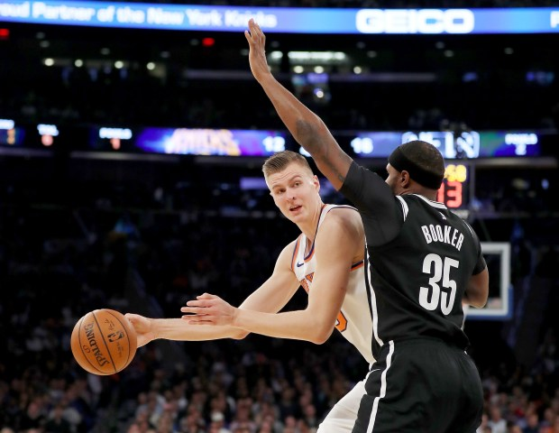Kristaps Porzingis of the New York Knicks tries to get around Trevor Booker of the Brooklyn Nets at Madison Square Garden on Oct. 27, 2017 in New York City.