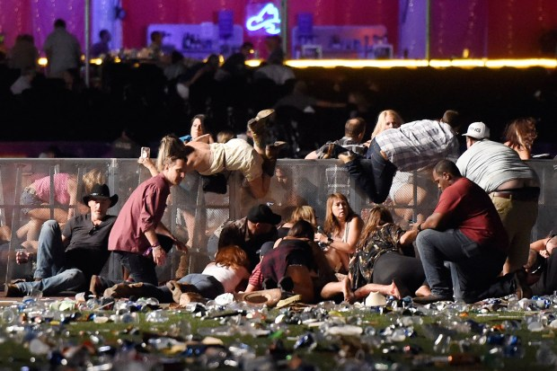 People scramble for shelter at the Route 91 Harvest country music festival in Las Vegas on Sunday night after a shooter opened fire from a nearby hotel. At least 58 people were killed and more than 500 injured in the worst mass shooting in U.S. history.