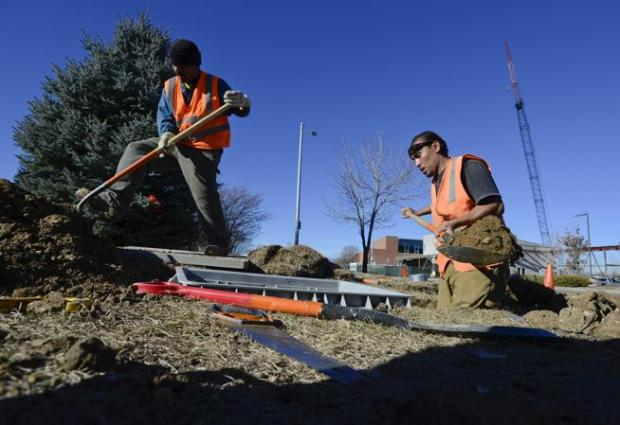 Systems Underground employees Angel Rangel, left, and Henry Moto, contracted by Longmont Power and Communications, work to install a junction box in the ground for the NextLight fiber-optic network Dec. 11 near Quail Road and South Emery Street in Longmont.