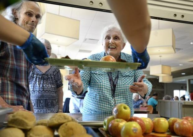 Carol Poore, center, and Jim McCullough, left, pick up a tray of food on July 9, 2015, from volunteer Tessa Anderson during senior lunch at Josephine Commons in Lafayette.