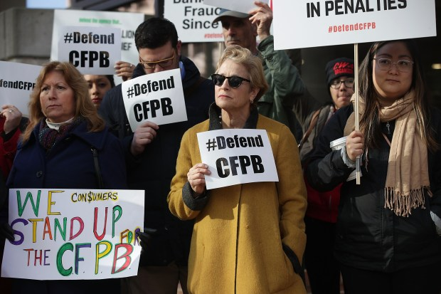 Supporters of the Consumer Financial Protection Bureau hold signs as they gather in front of the agency on Monday in Washington.