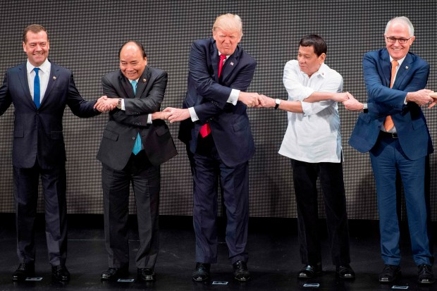 World leaders join hands for a photo during the opening ceremony of the Association of South East Asian Nations (ASEAN) Summit in Manila on Monday. From left: Russian Prime Minister Dmitry Medvedev; Vietnamese Prime Minister Nguyen Xuan Phuc; President Donald Trump; Philippine President Rodrigo Duterte; and Australian Prime Minister Malcolm Turnbull.