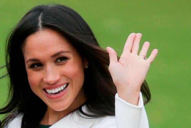 Meghan Markle waves as she poses for a photograph in the Sunken Garden at Kensington Palace in London on Monday. Markle is engaged to Britain's Prince Harry.