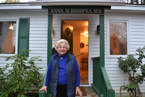 Dr. Anna Konopka stands in front of her tiny office where she sees patients, Thursday, Nov. 2, 2017 in New London, N.H.. A New Hampshire judge has denied the 84-year-old doctor's request to regain her license to practice, which she had surrendered partly over her inability to use a computer.