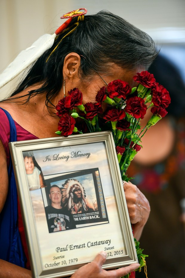 Lynn Eagle Feather buries her face in a bouquet of carnations while holding a sign in memory of her son, Paul Castaway, who was shot at killed by Denver police in 2015.
