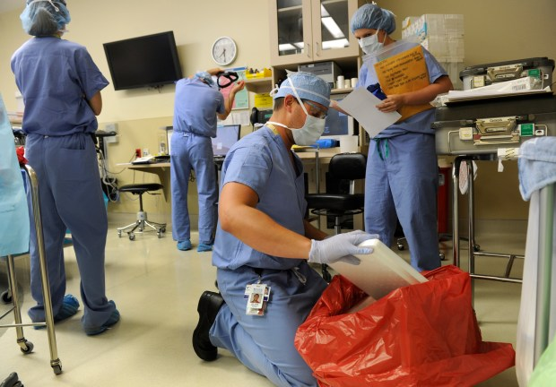 An organ recovery specialist for the Donor Alliance prepares a kidney to be transported from a donor in Denver to a recipient in Virginia on Aug. 23, 2013.