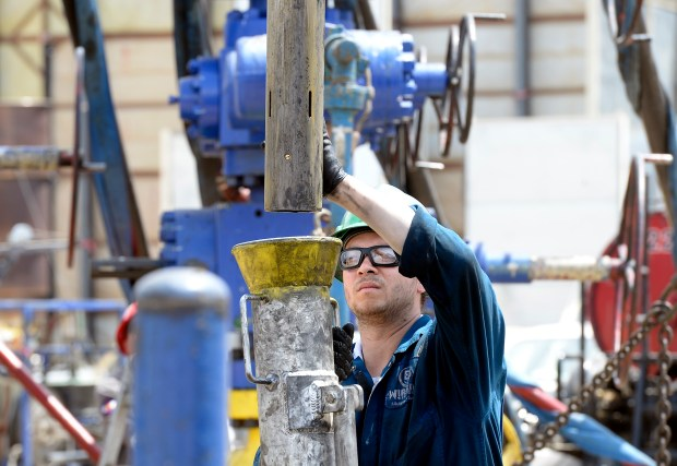 A Schlumberger Oil Field Services employee works on a fracking operation in Erie on June 28.