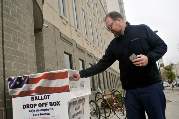 A voter drops off his ballot outside the Denver Elections Division headquarters downtown on Monday.