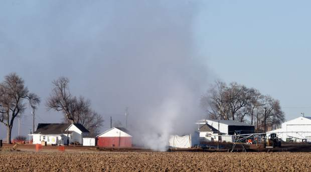 A plume of gas rises out of a field near a farm on Tuesday along Weld County Road 47 near the intersection of Weld County Road 60 1/2 east of Greeley. Emergency crews closed down the area until the leak could be brought under control.