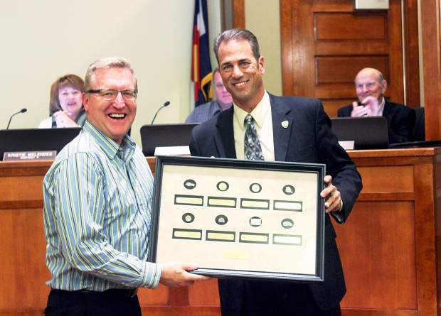 In this Nov. 9, 2015, file photo, then-town Manager Kelly Arnold accepts a plaque commemorating his 30-year career in city government from then-Windsor Mayor John Vazquez during a board meeting. Arnold resigned Tuesday. Neither Arnold nor Windsor officials provided a reason for his departure.