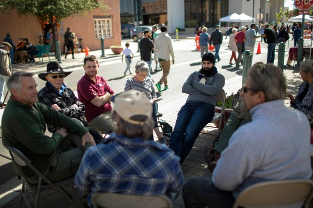 Mustafa Azimi, center, joins another farmers market discussion group hosted by Randy Harris, a friend, whose table is usually positioned near the Islamic Center's table.