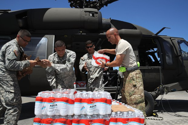 Puerto Rican National Guardsmen load a helicopter with food and water to bring to hurricane survivors as they deal with the aftermath of Hurricane Maria on Sept. 29 in San Juan.