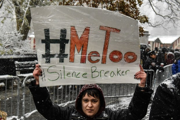 A woman carries a sign during a #MeToo rally outside of Trump International Hotel in New York City on Dec. 9.