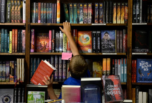 A boy reaches for a book on the top shelf in the Children's section of the Tattered Cover Book Store on Colfax Avenue in Denver on June 11, 2016. The number of independent bookstores nationally has jumped by over 30 percent since 2009, according to the American Booksellers Association.