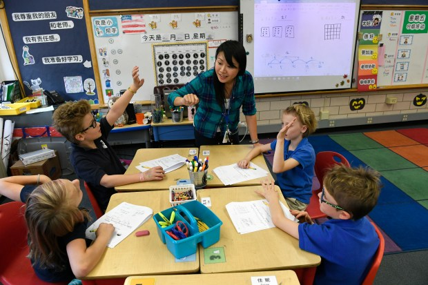Teacher Yu-Hsin Lien helps her third-grade students with classwork at the Denver Language School on Nov. 1. The Language Denver School is Denver's only full-language immersion K-8 charter school.