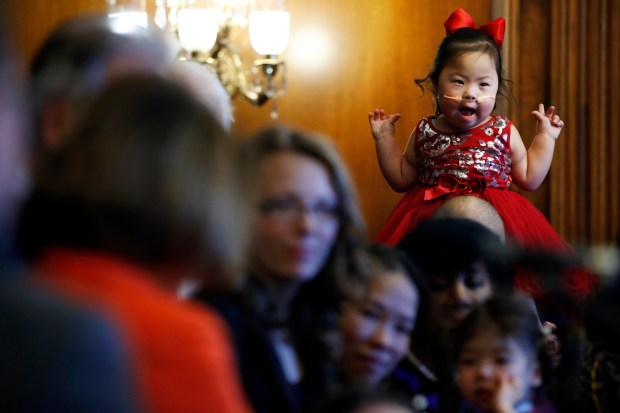 Melanie Carrigg, 5, who has Down syndrome, is deaf, and has Glycogen Storage Disease, plays on her father's shoulders while House Minority Leader Nancy Pelosi speaks during a news conference in opposition to the Republican tax bill on Dec. 19 at the U.S. Capitol.