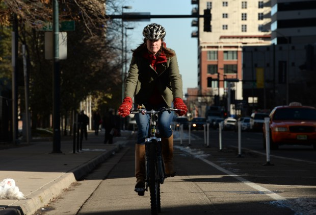 A woman rides her bicycle in a protected bike lane in downtown Denver on Dec. 3, 2015.