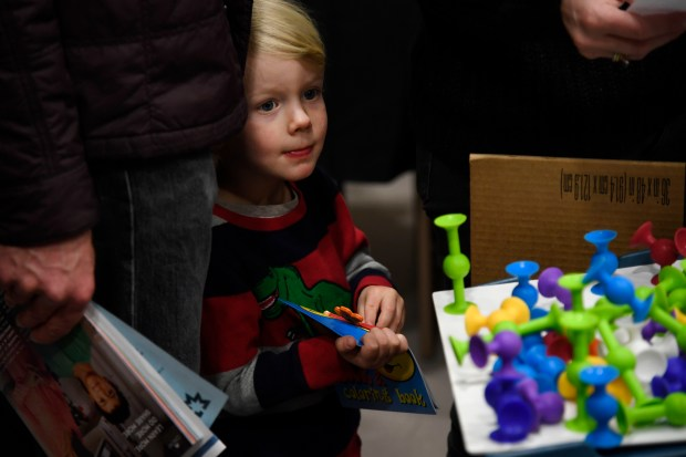 Soren Alauf, 3, checks out toys ...