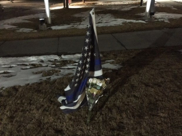 Flowers and a flag left at Adams County Sheriff's Office Substation at 4201 E. 72nd Ave.