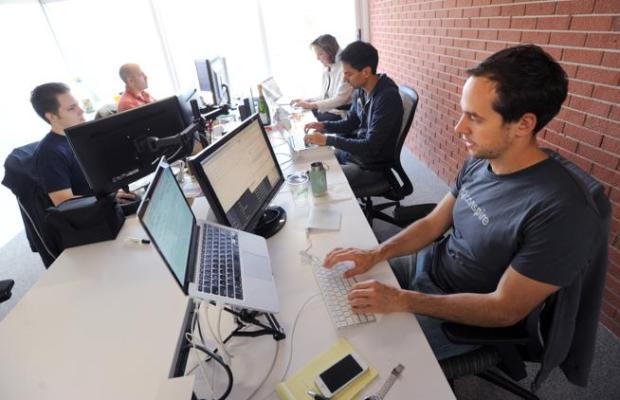 Paul McReynolds, right, counter-clockwise, Alex Devkar, Sarah Ross, Jeremy Frazao and Ryan Tanner, working at Conspire on Oct. 22, 2014. The Boulder startup shutdown this month.