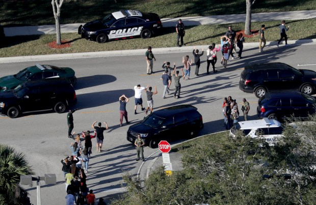 CORRECTS SPELLING TO MARJORY NOT MARJORIE Students hold their hands in the air as they are evacuated by police from Marjory Stoneman Douglas High School in Parkland, Fla., on Wednesday after a shooter opened fire on the campus. At least 17 people were killed in the shooting.